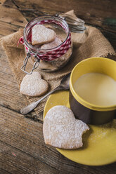 Preserving jar of heart-shaped shortbreads sprinkled with icing sugar and cup of milk - GIOF01809