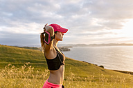 Young woman looking at the sea after workout - MGOF02889