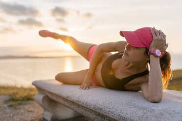 Young woman doing strength training on a bench at the sea - MGOF02892