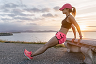 Young woman doing strength training on a bench at the sea - MGOF02895
