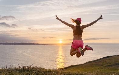 Female athlete jumping for joy - MGOF02901