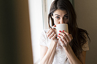 Portrait of woman drinking cup of coffee - KKAF00362