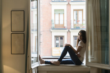 Woman sitting on window sill at open window - KKAF00377
