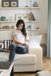 Woman sitting on couch at home using laptop - KKAF00383