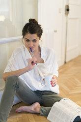 Pensive young woman sitting on the floor with coffee mug and ballpen - KKAF00389