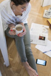 Young woman sitting on the floor drinking white coffee - KKAF00392