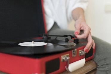 Woman using record player, close-up - KKAF00395
