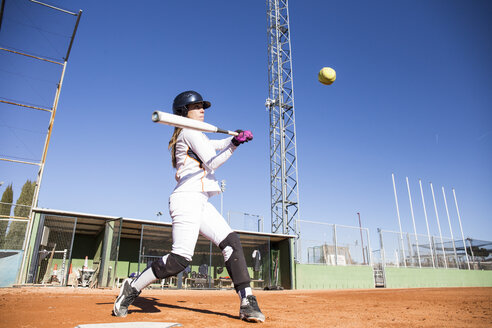 Female batter hitting the ball during a baseball game - ABZF01880