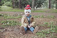 Portrait of boy wearing wooly hat sitting inforest - RTBF00626