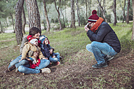 Father taking a picture of his family in forest - RTBF00635