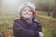 Portrait of grinning boy wearing wooly hat in forest - RTBF00647