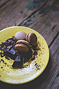 Different macarons and chocolate shaving on yellow dish - GIOF01811
