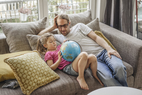 Father and daughter lying with globe on sofa - JOSF00484