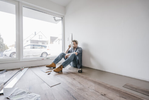 Mature man fitting flooring in new home, drinking coffee and taking a break - JOSF00492