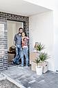 Happy couple standing in door of their new home - JOSF00495
