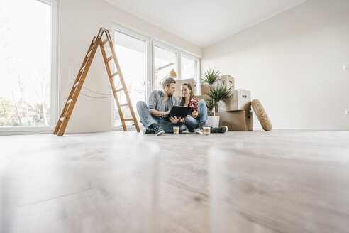 Couple sitting on floor of their new home among moving boxes - JOSF00504