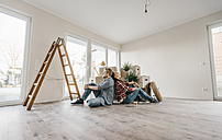 Couple sitting on floor of their new home among moving boxes - JOSF00507