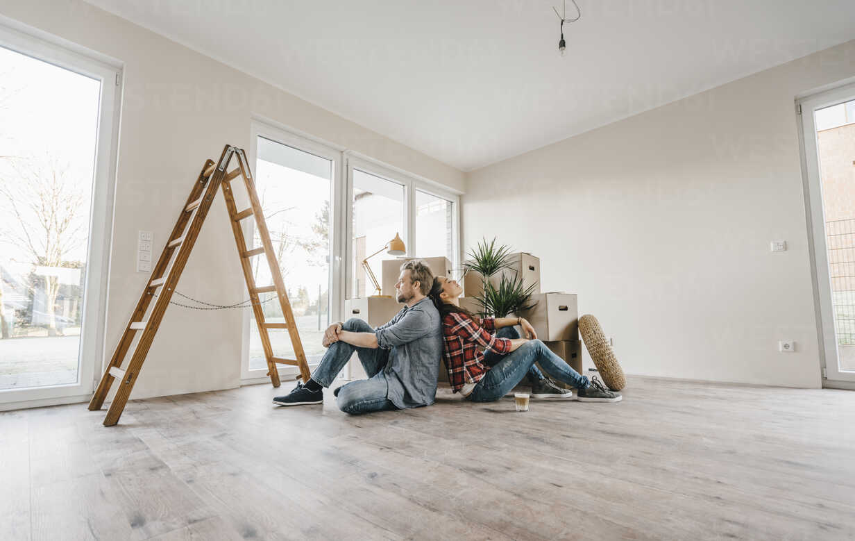 Couple sitting on floor of their new home among moving boxes - JOSF00507 - Joseffson/Westend61
