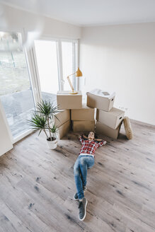 Mature woman moving house, lying on floor, thinking - JOSF00522