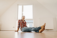 Mature woman moving house, sitting on floor, thinking - JOSF00525