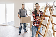 Couple moving house, carrying boxes in new home - JOSF00531