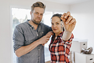 Couple moving house, woman holding keys of new home - JOSF00540