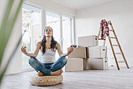 Woman sitting on cushion in her new apartment, meditating - JOSF00549