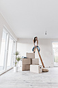 Mature woman sitting on ladder in her new home - JOSF00561
