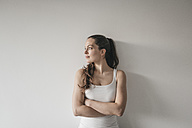 Woman leaning against wall with arms crossed - JOSF00564