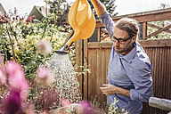 Man watering flowers in garden - JOSF00570