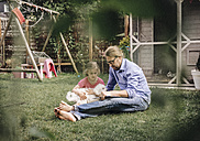 Father reading book with daughter in garden - JOSF00573