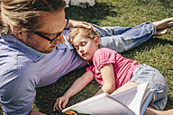 Father reading book to sleeping daughter in garden - JOSF00576