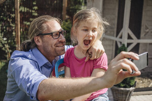 Father and daughter taking a selfie in garden - JOSF00579