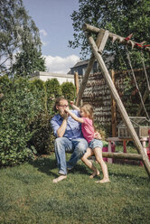 Father playing with daughter in garden - JOSF00582