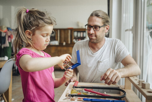 Father looking at daughter working with tools - JOSF00588