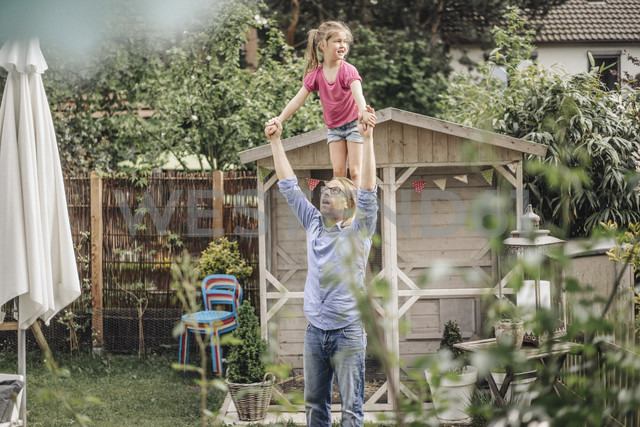 Father carrying daughter on shoulders in garden - JOSF00609