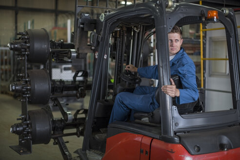 Factory working driving a fork lift in warehouse - ZEF12759