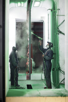 Painters spraying steel components in spray booth of a factory - ZEF12777