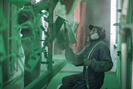 Painters spraying steel components in spray booth of a factory - ZEF12780