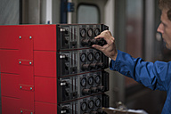 Factory worker in truck manufacture operating control panel - ZEF12783