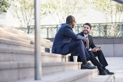 Two businessmen sitting on stairs talking - WESTF22580