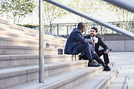 Two businessmen sitting on stairs talking - WESTF22583