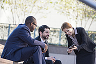 Businesspeople sharing tablet outdoors - WESTF22586