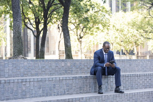 Businessman sitting on stairs using tablet - WESTF22598