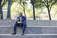 Businessman sitting on outdoor stairs having lunch - WESTF22601
