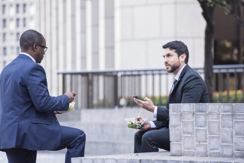 Two businessmen having lunch and talking outdoors - WESTF22604