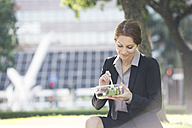 Businesswoman having lunch outdoors - WESTF22610
