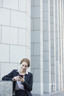 Smiling businesswoman using cell phone - WESTF22616