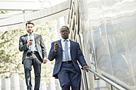 Two businessmen on the move looking at cell phones - WESTF22625