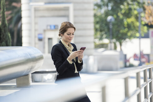 Businesswoman checking cell phone outdoors - WESTF22628